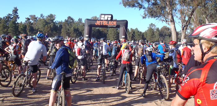 Mountain bike riders lining up at start arch