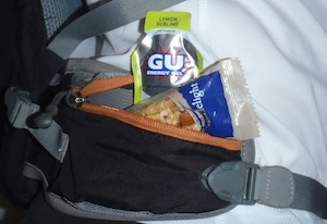 Hip pockets of pack with muesli bar and gu